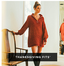 Thanksgiving 'Fits: woman in a red zip up sweater dress rests her hand on a chair in front of a mirror