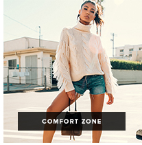 Comfort Zone: Woman in a frayed white turtleneck sweater and blue denim shorts holds a brown bag in a parking lot.
