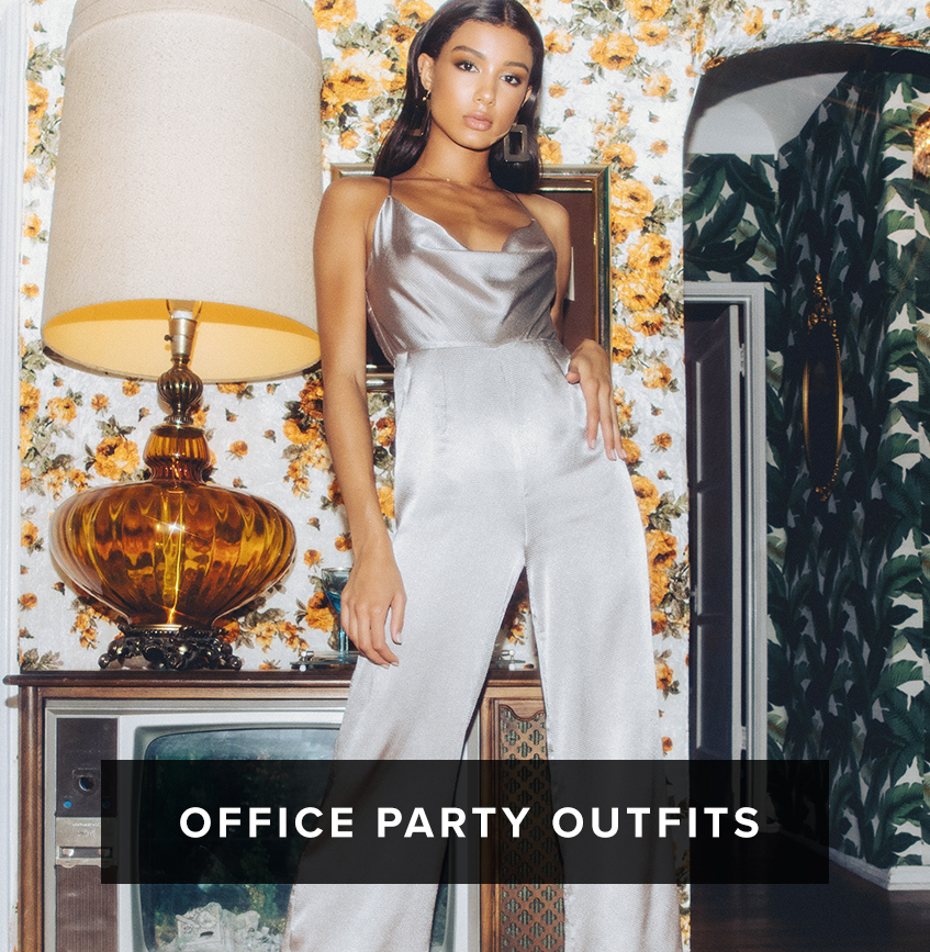 Office Party Outfits: dark haired woman in silver sleeveless cami cowl neck wide leg jumpsuit with square earrings