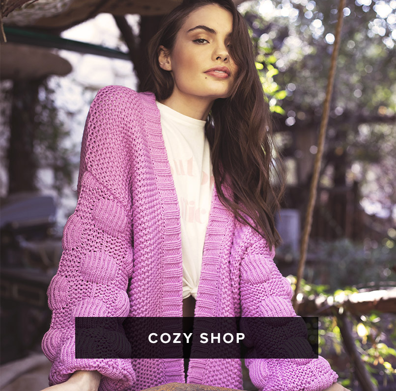 Cozy Shop: dark haired woman wears a purple open front bubble sleeve knitted cardigan over a white graphic crew neck t-shirt