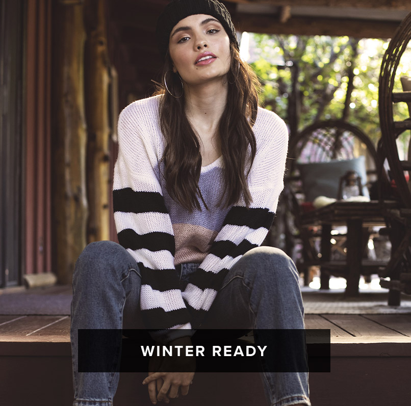 Winter Ready: dark long haired woman sits on porch and wears a black beanie and white sweater with striped sleeves and jeans