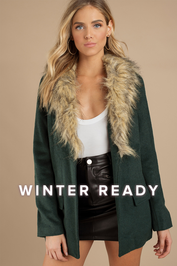 Winter Ready: blonde woman in a white tank top, black faux leather skirt, and green open front coat with faux fur collar