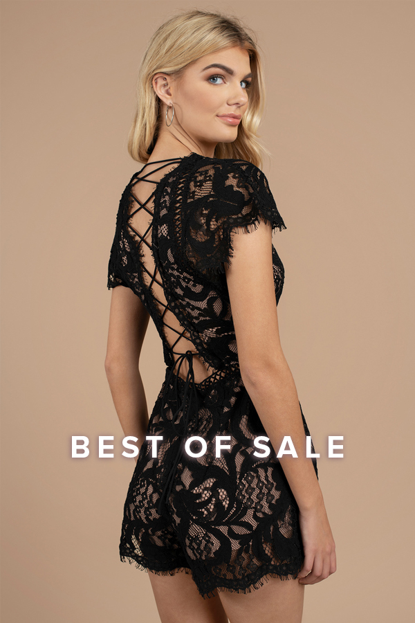 Best of Sale: blonde woman looking back wearing a black cap sleeve lace up lace romper in front of a beige background