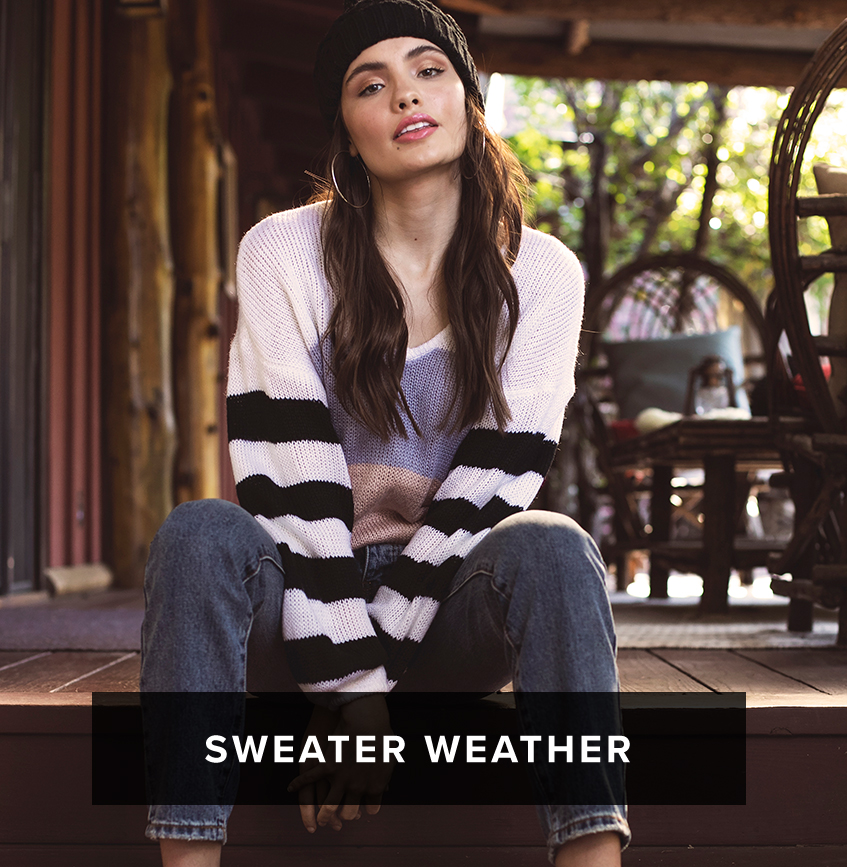 Sweater Weather: dark long haired woman sits on porch and wears a black beanie and white sweater with striped sleeves