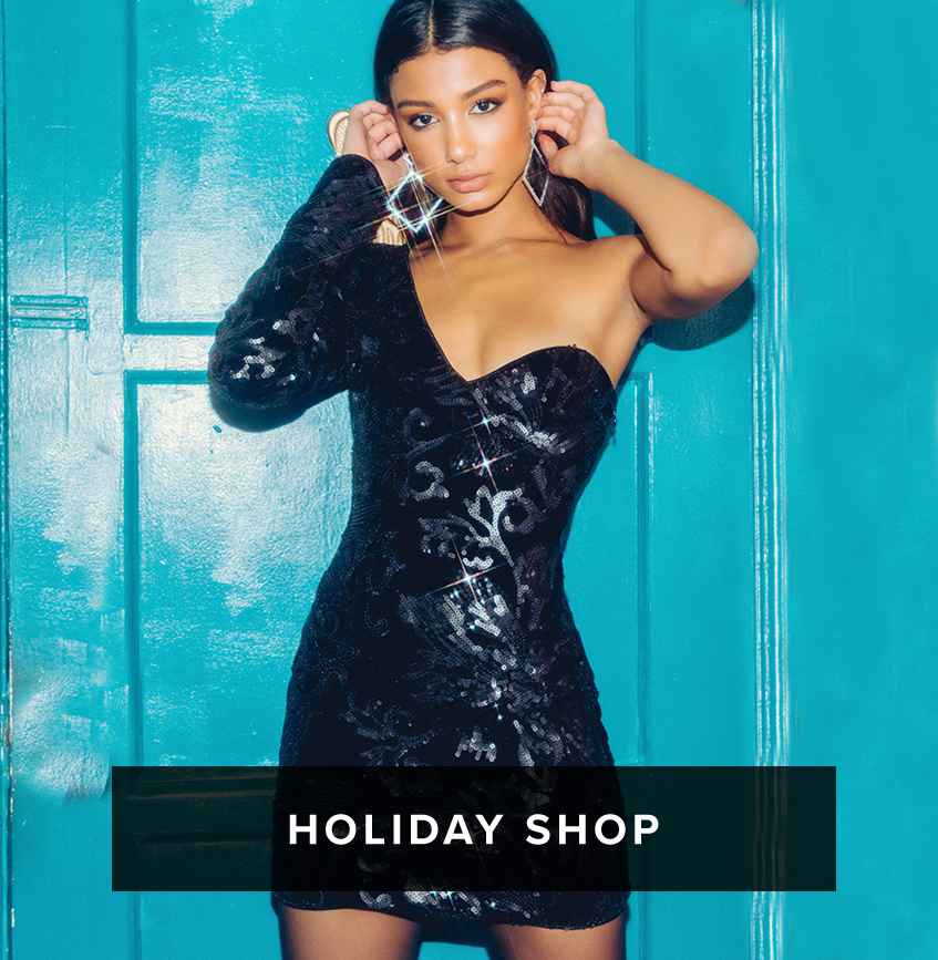 Holiday Shop: Shop Now. A dark haired woman wearing a tight one sleeved black sequin mini dress with a sweetheart neckline
