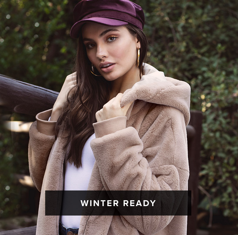 Winter Ready: dark haired woman wears a purple cadet hat and a white blouse under a beige oversized hooded faux fur coat