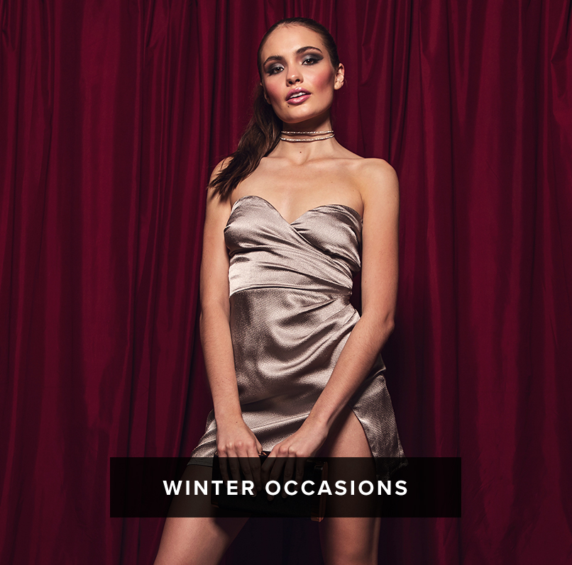 Winter Occasions: dark haired woman wears a silver strapless ruched mini dress with a sweetheart neckline and thigh high slit