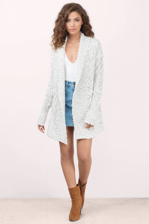 This long sleeve cardigan has an open front construction and is made with a cozy waffle knit. This comfy layering piece has two front pockets and ribbed knit details. Available in a neutral cream coloring, this Waffle Knit Cardigan Sweater from Fate will be your go-to layering piece for the season.